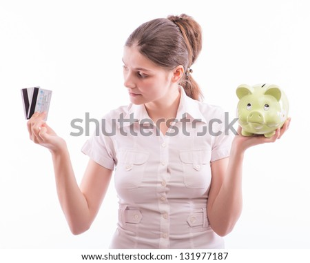 Woman holding piggy bank and card - stock photo