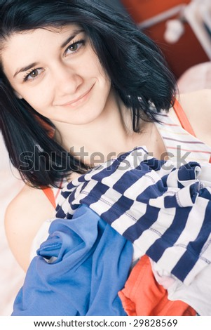 Woman holding pile of laundry smiling - stock photo