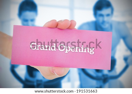 Woman holding pink card saying grand opening against fitness class in gym - stock photo
