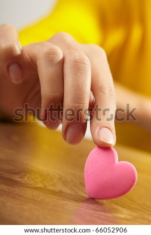 Woman holding pink heart in the hand - stock photo
