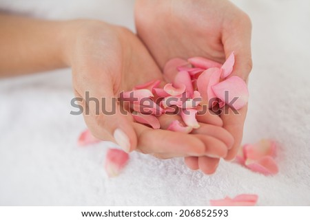 Woman holding pink rose petals at the health spa - stock photo