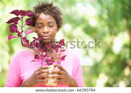 Woman holding plant with eyes closed - stock photo