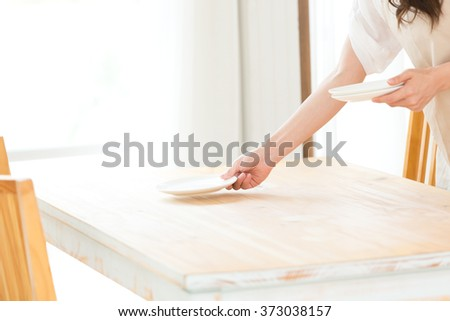 Woman holding plates and dishes in her kitchen - stock photo