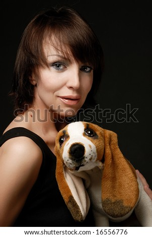 Woman holding plush dog looking at the camper smiling - stock photo