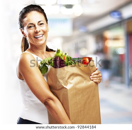 woman holding purchase at a crowded place - stock photo