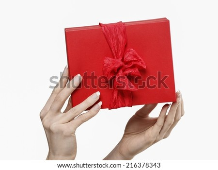 Woman holding red present box with big bow isolated on a white background - stock photo