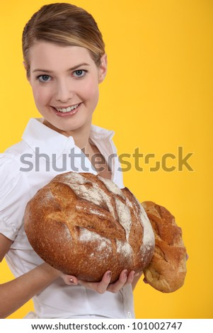 Woman holding round loaves of bread - stock photo