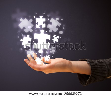 Woman holding shining puzzle pieces in her hand - stock photo