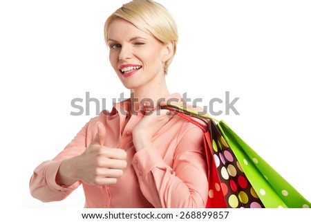 Woman holding shopping bag and showing ok, isolated on white background - stock photo