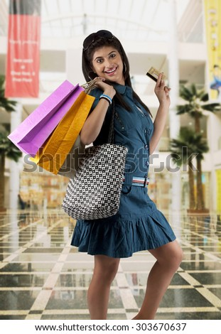 Woman holding shopping bags and a credit card - stock photo