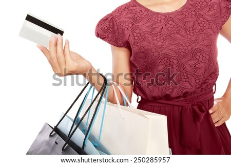 Woman holding shopping bags and credit cards, isolated on white background - stock photo