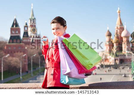 Woman holding shopping bags and showing credit card in front of Spasskaya tower - stock photo