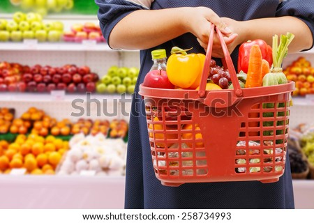 woman holding shopping basket in supermarket,fruit zone background - stock photo