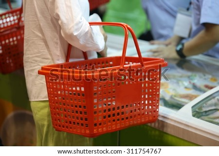 woman holding shopping basket in supermarket, Thailand, spending money with food and beverage. - stock photo
