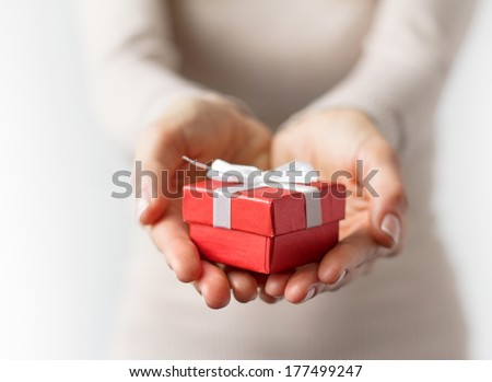 Woman holding small red present box in hands. - stock photo