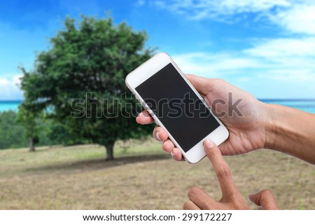 Woman holding smartphone against spring green or mobile phone with blank mobile.Shallow depth of field. - stock photo
