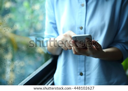 Woman holding smartphone with touch on screen - stock photo