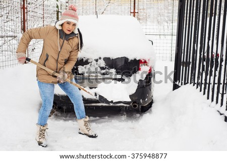Woman holding snow shovel and cleaning  path  by snow - stock photo