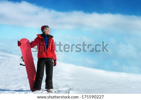 Woman holding snowboard and looking away - stock photo