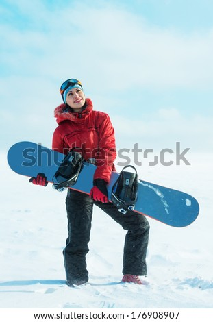 Woman holding snowboard and looking up - stock photo