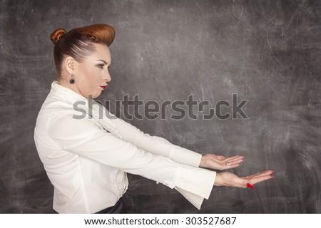 Woman holding something heavy on the blackboard background - stock photo