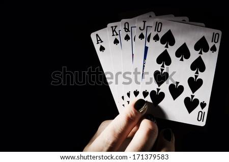 woman holding spades royal flush. poker game. - stock photo