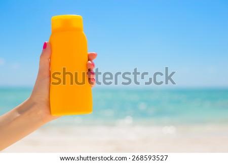 Woman holding sunscreen bottle - stock photo