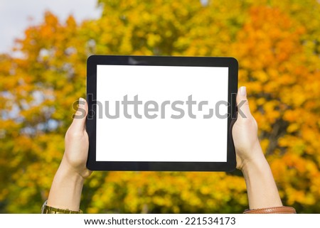 Woman holding tablet in hand autumn - stock photo