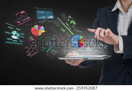 Woman holding tablet pc with graphs and diagrams flying out. Statistics concept. - stock photo
