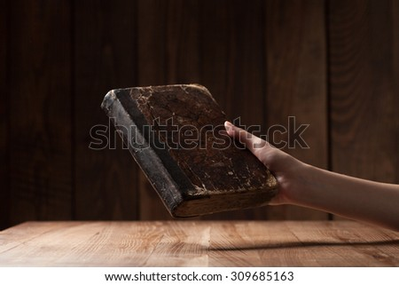 woman holding the bible in the darkness over wooden table - stock photo