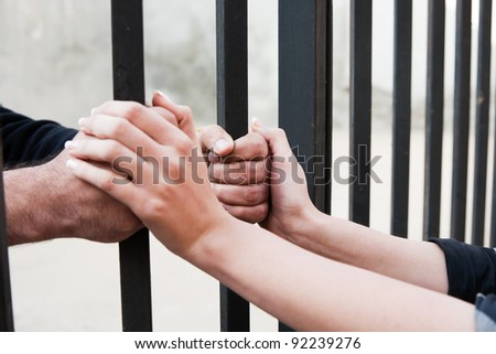 woman holding the hands of her husband behind the bars - stock photo