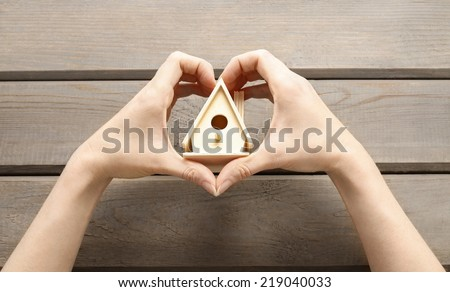 Woman holding tiny wooden house - stock photo