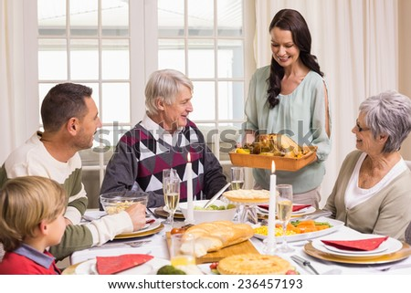 Woman holding turkey roast with family at dining table at home in the living room - stock photo