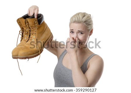 woman holding up a pair of mens smelly shoes not looking very happy - stock photo