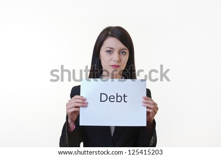 woman holding up a piece of paper with the word debt written on it and tearing the sheet of paper in half - stock photo