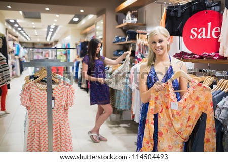 Woman holding up orange shirt in clothing store - stock photo