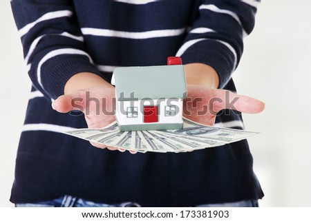 Woman holding US dollars bills and house model over white - real estate loan concept  - stock photo