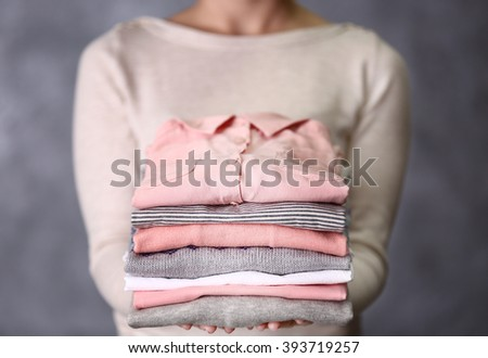 Woman holding washed and dried clothes on grey background - stock photo