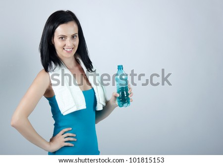 Woman holding water bottle while smiling - stock photo