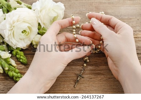 Woman holding wooden rosary in hands. White persian buttercup flowers (ranunculus) in the background - stock photo
