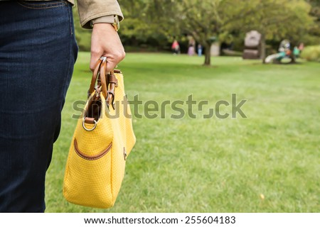 Woman holding yellow purse - stock photo