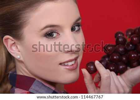 Woman holdingf red grapes - stock photo