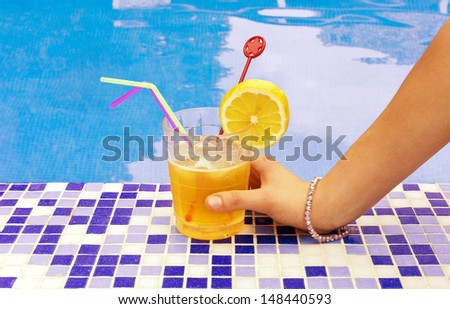 woman holds a glass with your hand by the pool border - stock photo