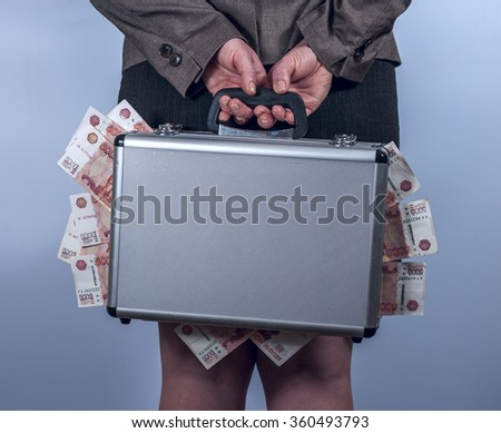 Woman holds a suitcase with money behind the back - stock photo