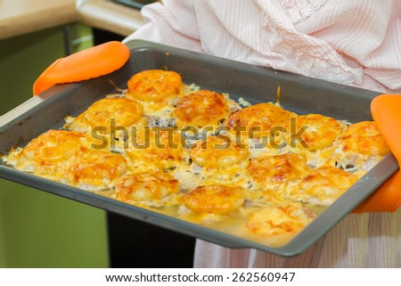 Woman holds appetizing hot roasted meat with cheese and pineapples baked in oven - stock photo
