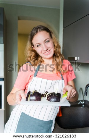 Woman holds board with cut eggplant - stock photo