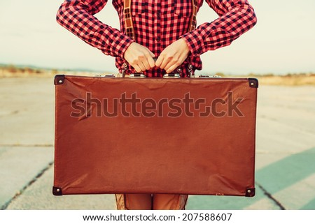Woman holds brown vintage suitcase, face is not visible, copy-space - stock photo