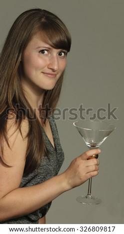 Woman holds empty martini glass - stock photo