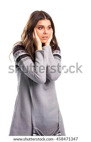 Woman holds face with hands. Scared lady in gray sweater. The news is shocking. This can't be true. - stock photo