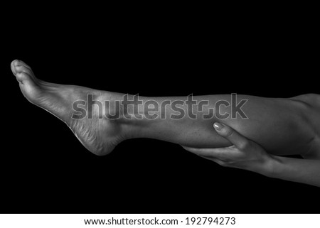 Woman holds her leg, pain in the female calf muscle, monochrome image - stock photo